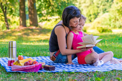 Mom and daughter reading a book on the lawn Royalty Free Stock Images