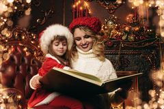 Reading christmas tale. Mom and daughter reading a Christmas tale in beautiful decorated apartments. Time for miracles royalty free stock photography