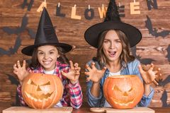 Mom and daughter ready for Halloween. Cute little girl and her beautiful mom in witch hats are showing claws at camera while sitting on wooden background Stock Photo
