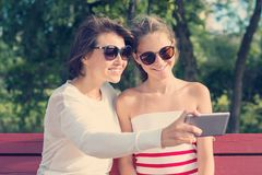 Mom and daughter, relationship between parent and teenager, outdoor portrait of mother with girl having fun, taking photos on mobi. Le phone royalty free stock image
