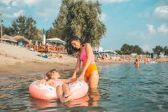 Mom and daughter having fun in the water on an inflatable donut stock images
