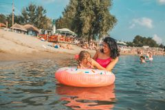 Mom and daughter relaxing on an inflatable donut royalty free stock images