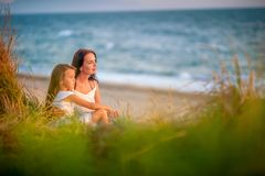 Mom and daughter rest on the beach, sit on the beach royalty free stock photos