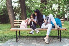 Mom and daughter rest on the bench. In the park Royalty Free Stock Photo