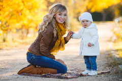 Mom and daughter resting in a park in autumn. A young mother with her small daughter for a walk in the Park on a Sunny autumn day,mom is a beautiful blonde with Royalty Free Stock Photography