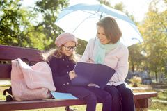 Mom and daughter are resting together on a bench in the city park, the girl in glasses reads to her mother a school notebook royalty free stock images