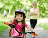 Mom and daughter ride bikes in the forest Stock Photography