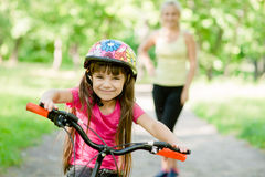 Mom and daughter ride bikes in the forest Stock Images