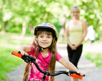 Mom and daughter ride bikes in the forest Stock Image