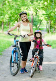 Mom and daughter ride bikes in the park Stock Image