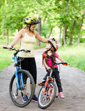 Mom and daughter ride bikes in the park Royalty Free Stock Image