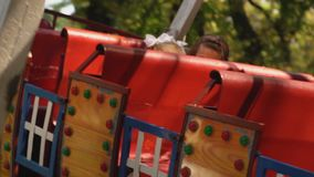 Mom and daughter ride a ship-like ride stock video footage