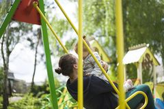 Mom and daughter ride on a swing in a children park.mother rolls a little girl on a swing stock images