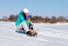 Mom and daughter rideing on sledge Royalty Free Stock Photo