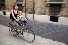 Mom with daughter riding bike in Italy. Child sitting in safety. Seat. Old narrow italian town. Sport healthy family activity. Summer european vacation. Happy stock photos
