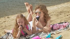 Mom and daughter on the river bank eat ice cream. Outdoor recreation. Mom with her daughter, a young woman in a white swimsuit and a little girl in pink clothes stock video footage
