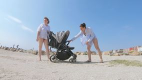 Mom and daughter are rocking. On the sea beach grandmother and young mother rocked the baby in stroller stock video