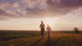 Mom and daughter run in a picturesque place at sunset. Active lifestyle and healthy family. 4K slow motion video stock footage