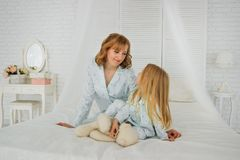 Mom and daughter in the same pajamas on the bed. Face to Face. They look at each other. stock image