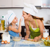 Mom and daughter sheeting dough. Happy mom and little daughter sheeting dough and smiling Royalty Free Stock Images