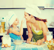 Mom and daughter sheeting dough Stock Image