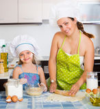 Mom and daughter sheeting dough Royalty Free Stock Photos