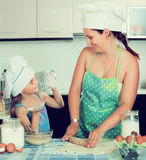 Mom and daughter sheeting dough. Positive mom and little daughter sheeting dough and smiling Royalty Free Stock Image