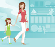 Mom and Daughter Shopping. Cute Mom and her excited daughter shopping together at a toy store Stock Image