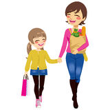 Mom Daughter Shopping Together. Beautiful mom with grocery paper bag and daughter shopping together helping parent holding bags Stock Photo