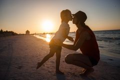 Mom and daughter silhouette in the sunset at the Stock Images