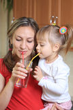 Mom and daughter sipping water together Stock Images