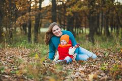 Mom and daughter sit on the foliage in the autumn park royalty free stock photos
