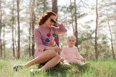 Mom and daughter sit on the grass and play air mill. The girl shows the child a toy windmill, the two of them sitting on the grass in the Park, dressed in pink royalty free stock image