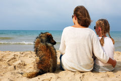 Mom and daughter sit hugging on the sea and look at the water. Stock Photography