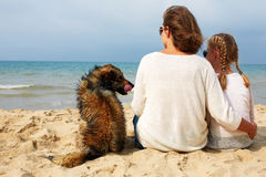 Mom and daughter sit hugging on the sea and look at the water. Royalty Free Stock Photography
