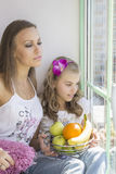 Mom and daughter sit near the window. They look to the street. The girl fruit basket Royalty Free Stock Photo