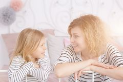 Mom and daughter sitting. On the bed and smiling stock image