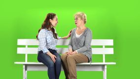 Mom and daughter are sitting on a bench. Green screen. Mom and daughter are sitting on a bench and talking on talking on various topics. Green screen stock footage
