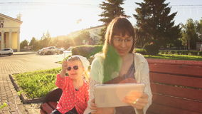 Mom and daughter are sitting on a bench on a square near the road at sunset. stock footage