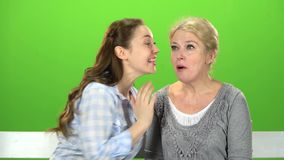 Mom and daughter are sitting on a bench. Green screen. Mom and daughter are sitting on a bench and talking on talking on various topics. Green screen stock video footage