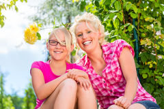 Mom and daughter sitting in garden enjoying Royalty Free Stock Photos