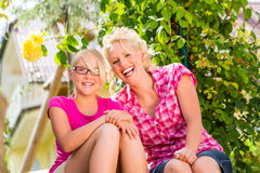 Mom and daughter sitting in garden enjoying sunshine Royalty Free Stock Photo