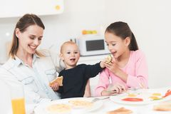 Mom and daughter are sitting in the kitchen and having breakfast. They have fun at breakfast. Mother is holdin a baby on her arms royalty free stock images