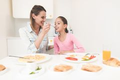 Mom and daughter are sitting in the kitchen and having breakfast. They have fun at breakfast. Mom and daughter are in a bright room Royalty Free Stock Image