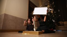 Mom and daughter sitting under the Christmas tree open gifts. The girl untying the ribbon of the gift. Overall plan stock video