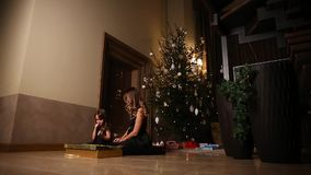 Mom and daughter sitting under the Christmas tree open gifts. Overall plan stock footage