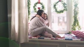 Mom and daughter are sitting at the window on the background of Christmas decorations. happy family mom and baby