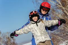 Mom and daughter, in ski equipment play with snow Royalty Free Stock Photography