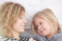 Mom and daughter smiling. Happy mom and little daughter smiling at each other stock photo