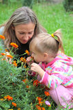 Mom and daughter sniffing flowers in the garden Royalty Free Stock Images